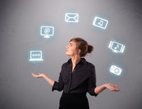 Pretty girl juggling with elecrtonic devices icons. Pretty girl standing and juggling with elecrtonic devices icons Royalty Free Stock Images