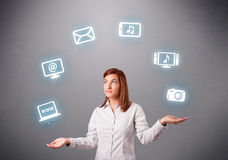 Pretty girl juggling with elecrtonic devices icons Stock Image