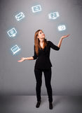 Pretty girl juggling with elecrtonic devices icons Royalty Free Stock Images