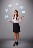 Pretty girl juggling with elecrtonic devices icons Royalty Free Stock Photography