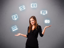 Pretty girl juggling with elecrtonic devices icons. Pretty girl standing and juggling with elecrtonic devices icons Stock Image