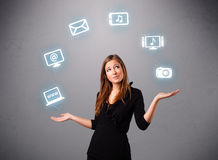 Pretty girl juggling with elecrtonic devices icons Stock Photos