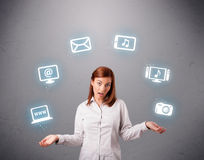 Pretty girl juggling with elecrtonic devices icons Stock Photo
