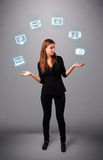 Pretty girl juggling with elecrtonic devices icons Royalty Free Stock Photos