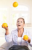 Pretty girl juggling with grapefruits in bed Royalty Free Stock Images