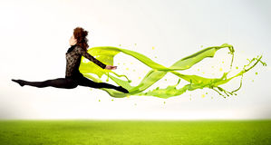 Pretty girl jumping with green abstract liquid dress Stock Images