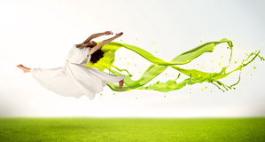 Pretty girl jumping with green abstract liquid dress stock photo