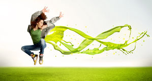 Pretty girl jumping with green abstract liquid dress Royalty Free Stock Images