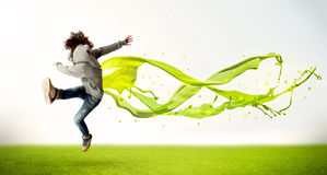 Pretty girl jumping with green abstract liquid dress Stock Image
