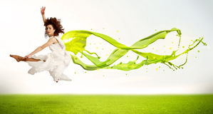 Pretty girl jumping with green abstract liquid dress Royalty Free Stock Photos
