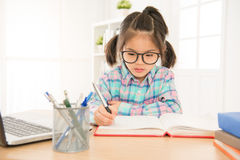 Pretty girl kid wear glasses seriously writing. Pretty cute girl kid wear glasses seriously writing homework with laptop computer on the desk in study room stock image