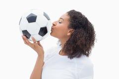 Pretty girl kissing her football Stock Photo