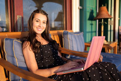 Pretty girl with laptop. Beautiful girl with a laptop computer in the patio of a home Royalty Free Stock Photo