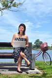 Pretty girl with laptop and bicycle at  lake Royalty Free Stock Photos