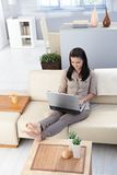 Pretty girl with laptop in cosy room Stock Images