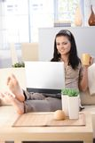 Pretty girl with laptop at home smiling Stock Images