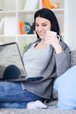 Pretty girl with laptop at home smiling Stock Photography