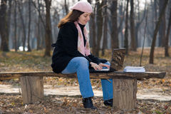 Pretty girl with laptop outdoor. Young, pretty woman, using a laptop computer outdoor, sitting on a bench in park Royalty Free Stock Image
