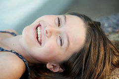 Pretty girl laughing. Natural headshot portrait of young and pretty girl laughing and looking at the camera royalty free stock image