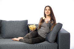 Pretty girl laughing, watching tv, sitting on sofa Royalty Free Stock Image