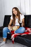 Pretty girl laughing, watching tv, sitting on sofa at home. Stock Photo