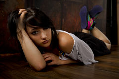 Pretty girl laying down on wooden floor with grunge background Stock Photo