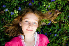 Pretty girl laying in periwinkle plant Stock Images