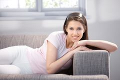 Pretty girl laying on sofa smiling Stock Photos