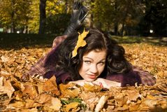 Pretty girl lays on the fallen leaves Royalty Free Stock Images