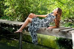 Pretty girl lays on pedestrian bridge. Attractive young woman lays on a wooden bridge outdoors royalty free stock photography