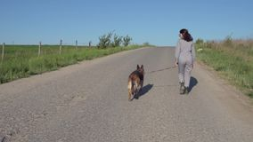 A pretty girl leads a dog next to her on the road