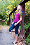 Pretty Girl Leaning on Bridge. Pretty teenage girl leaning on a bridge looking thoughtful Royalty Free Stock Images