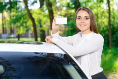 Pretty girl leaning on car and showing card Stock Photo