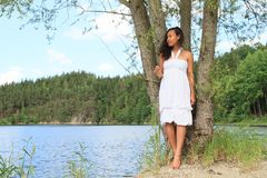 Pretty girl leaning on tree by Dam Rimov. Pretty Papuan girl - young barefoot woman in white dress leaning on trunk of tree and posing by water of Dam Rimov in royalty free stock photo