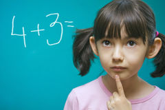 Pretty girl learning math. Schoolgirl stay near school blackboard. Close up Royalty Free Stock Image