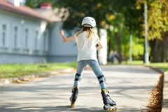 Pretty girl learning to roller skate on beautiful summer day in a park. Child wearing safety helmet enjoying roller skating ride. Pretty young girl learning to royalty free stock images
