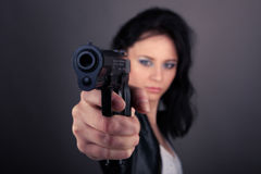 Pretty girl in leather jacket with gun in hands on a gray Royalty Free Stock Images