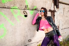 Pretty girl in leather jacket smokes. Young beautiful woman in sunglasses with spray paint smokes at wall background Royalty Free Stock Photos