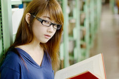 Pretty girl in library. Asian pretty girl reading the book in public library Royalty Free Stock Photos