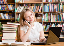 Pretty girl in library typing on laptop and talking on the phone Royalty Free Stock Images