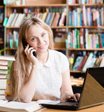 Pretty girl in library typing on laptop and talking on the phone Royalty Free Stock Image