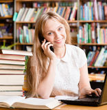 Pretty girl in library typing on laptop and talking on the phone Royalty Free Stock Photos