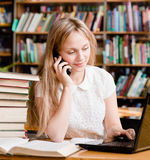 Pretty girl in library typing on laptop and talking on the phone.  royalty free stock photography