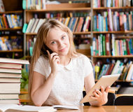 Pretty girl in library using tablet computer and talking on the phone Royalty Free Stock Photography