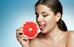 Pretty girl licking grapefruit Royalty Free Stock Photography