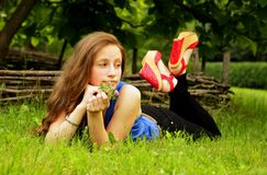 Pretty girl lies on the lawn with green grass and looks into the distance. Girl resting on the lawn with green grass Royalty Free Stock Photo