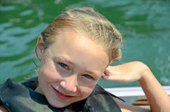 Pretty girl in Life Jacket. A wet young girl at the water wearing a life preserver for safety stock images