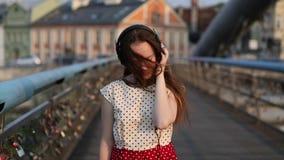 Pretty girl listening music in headphones on the bridge of love with locks. stock video