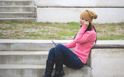 Pretty girl listening music with her headphones. Outside Royalty Free Stock Photo