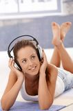 Pretty girl listening music laying on floor Royalty Free Stock Images